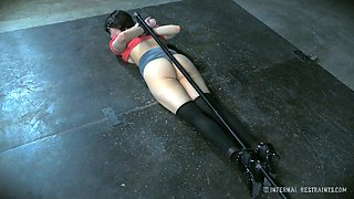 Sexy slut tied up to a long stick is lying on the floor