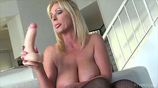 Blonde MILF with massive tits rams her fist in her snatch