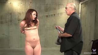 Submissive amateur redhead tied up and abused in a fetish scene