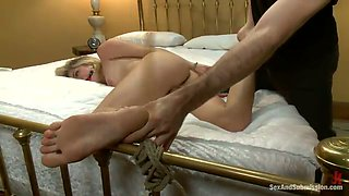 Bondage blonde with gag ball in her mouth hole is punished on the bed