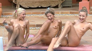 Three skinny blonde teens in swimsuits having morning exercises.