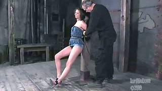 Tied to a pole brunette gets punished in the dark room